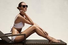 Brunbränd kvinna som solbadar på strandstol royaltyfri bild