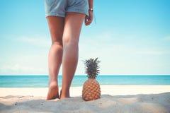 Brunbrända ben av anseendet för ung kvinna med ananas på den tropiska stranden i sommar Royaltyfria Foton