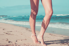 Brunbrända sexiga ben av en kvinna mot havet, tropisk strandplats, Bali ö Arkivfoton