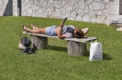 Brunbränd kvinna som ligger på en elektronisk bok för bänk och för läsning Royaltyfria Bilder