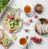 Brunch with avocado salad and flatbread, topview. Yummy brunch with avocado salad, ripe tomatoes and flatbread with dip on it, topview Stock Photography