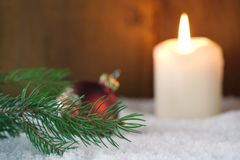 Brunch of Christmas tree with candle. Branch of Christmas tree with a burning candle and Christmas ball in snow Stock Image