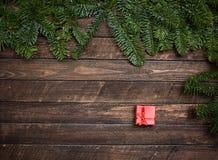 Brunch dell'albero di abete di Natale e poco contenitore di regalo rosso su legno rustico Fotografia Stock Libera da Diritti