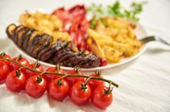 Brunch of fresh cherry tomatoes on white cloth close up. Fried potatoes, eggplant, bell pepper and cauliflower on white plate. Decorated with fork on blurred Stock Image