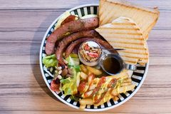 Brunch with german sausage, cereal, French fries and toast. Brunch with german sausage, cereal, French fries, salad and toast shot from above Stock Image