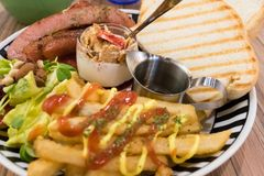 Brunch with german sausage, cereal, French fries and toast. Brunch with german sausage, cereal, French fries, salad and toast in plate Royalty Free Stock Images