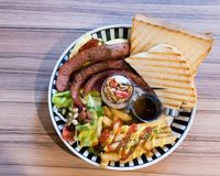 Brunch with german sausage, cereal, French fries and toast. Brunch with german sausage, cereal, French fries, salad and toast shot from above Royalty Free Stock Photo