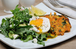 Brunch Idea. Egg poached with pumpkin spinach pancakes and garnish from arugula, avocado, mint leaves, and ricotta Stock Photo