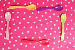 Brunch invitation. Five colorful spoons on pink dotted background stock photography