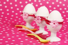Brunch invitation. Three egg cups with spoons on pink dotted background Royalty Free Stock Photos