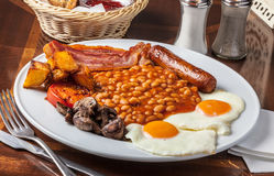 Brunch platter. With sausage, eggs, bacon, beans, potatoes, tomato and mushrooms Stock Photo