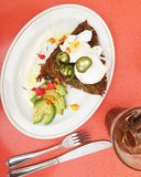 Brunch: potato and squash latke, poached eggs, avocado, jalapeños, flowers Royalty Free Stock Photos