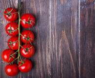 Brunch of ripe red cherry tomatoes. On the wooden table, top view Stock Photos