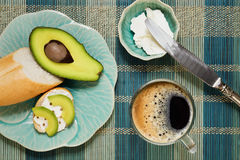 Brunch with spreading cheese, coriander and avocado. Original breakfast variety with fresh baguette bread, avocado, coriander and spreading cheese with a big cup stock images