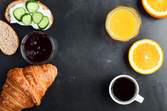 Brunch table with toasts, croissant, orange juice and coffee, to. Toasts, croissant, orange juice and coffee on rustic blue table, brunch table viewed from above Royalty Free Stock Images