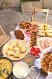 Brunch. Table with various brunch food: goat cheese and pear sandwiches, ham, croissants, scrambled eggs, mushroom tart, blueberry muffins, banana bread, cream Stock Image