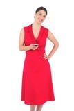 Brune élégante heureuse dans le service de mini-messages rouge de robe Images libres de droits