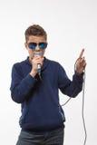 Brune émotive de garçon d'adolescent dans des lunettes de soleil avec un microphone Photo stock