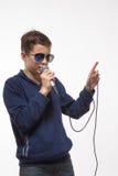 Brune émotive de garçon d'adolescent dans des lunettes de soleil avec un microphone Photos libres de droits