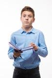 Brune émotive de garçon d'adolescent dans une chemise bleue avec un journal intime et un stylo à disposition Photo libre de droits