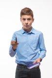 Brune émotive de garçon d'adolescent dans une chemise bleue avec un journal intime et un stylo à disposition Images libres de droits