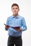 Brune émotive de garçon d'adolescent dans une chemise bleue avec un journal intime et un stylo à disposition Photos stock
