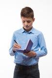 Brune émotive de garçon d'adolescent dans une chemise bleue avec un journal intime et un stylo à disposition Images stock