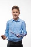 Brune émotive de garçon d'adolescent dans une chemise bleue avec un journal intime et un stylo à disposition Image stock