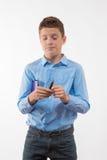 Brune émotive de garçon d'adolescent dans une chemise bleue avec un journal intime et un stylo à disposition Image libre de droits