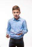 Brune émotive de garçon d'adolescent dans une chemise bleue avec un journal intime et un stylo à disposition Photographie stock