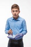 Brune émotive de garçon d'adolescent dans une chemise bleue avec un journal intime et un stylo à disposition Photo stock