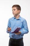 Brune émotive de garçon d'adolescent dans une chemise bleue avec un journal intime et un stylo à disposition Photographie stock libre de droits