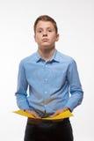 Brune émotive de garçon dans une chemise bleue avec la feuille de papier jaune pour des notes Photo stock