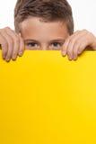 Brune émotive de garçon dans une chemise bleue avec la feuille de papier jaune pour des notes Images stock