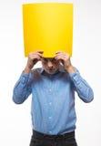 Brune émotive de garçon dans une chemise bleue avec la feuille de papier jaune pour des notes Images libres de droits