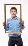 Brune émotive de garçon dans une chemise bleue avec un cadre de tableau dans les mains Images libres de droits
