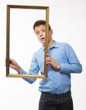 Brune émotive de garçon dans une chemise bleue avec un cadre de tableau dans les mains Photo libre de droits