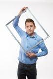 Brune émotive de garçon dans une chemise bleue avec un cadre de tableau dans les mains Image stock
