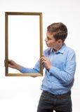 Brune émotive de garçon dans une chemise bleue avec un cadre de tableau dans les mains Photos stock