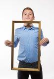 Brune émotive de garçon dans une chemise bleue avec un cadre de tableau dans les mains Photo stock