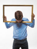 Brune émotive de garçon dans une chemise bleue avec un cadre de tableau dans les mains Image libre de droits
