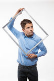 Brune émotive de garçon dans une chemise bleue avec un cadre de tableau dans les mains Photos libres de droits