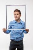 Brune émotive de garçon dans une chemise bleue avec un cadre de tableau dans les mains Photographie stock libre de droits