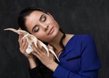 Brune attrayante avec un seashel Photographie stock libre de droits