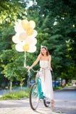 Brune attrayante de sourire tenant des ballons tout en conduisant le vélo bleu sur l'allée de parc Images stock