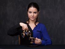 Brune attrayante gardant une tasse et un pot de lait Photographie stock