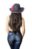 Brune aux cheveux longs dans un chapeau et des blues-jean posant avec le sien de retour images stock