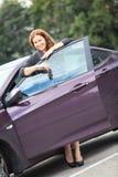 Brune avec des clés se tenant près juste de la voiture achetée Photo stock