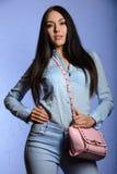 Brune avec du charme avec de longs cheveux tenant un sac à main rose Photographie stock libre de droits