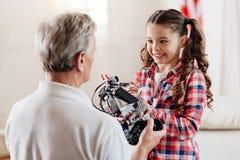 Brune avec du charme prenant le robot de jouet Images stock